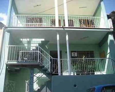 Casa de dos plantas verde con amplios balcones en ambos niveles..