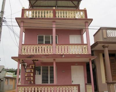 Frente de la casa color rosado.